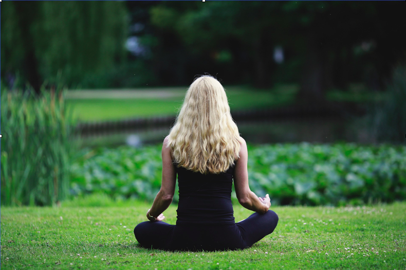 Woman practicing mindfulness by a pond